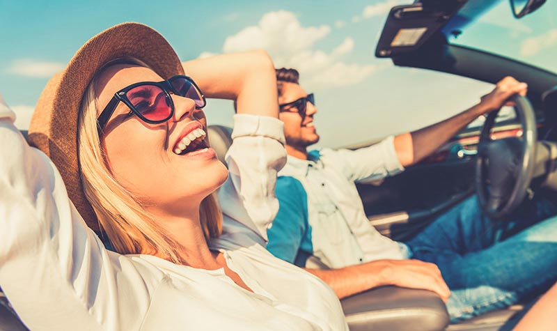 Man and woman riding in convertible car
