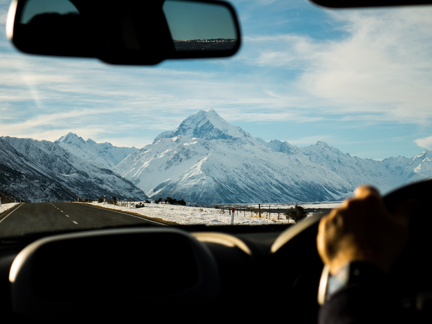 man driving towards mountains