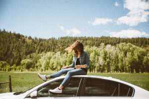 girl on top of car with woods in background